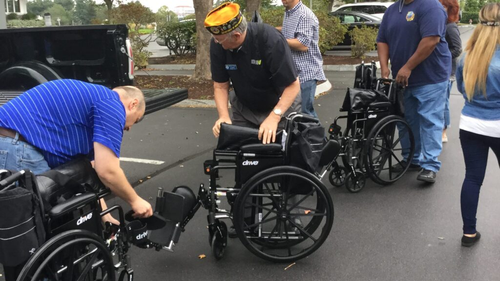 Employees giving a wheelchair to PWD